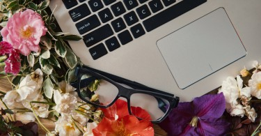 Creative workspace with beautiful flowers and mobile technology.